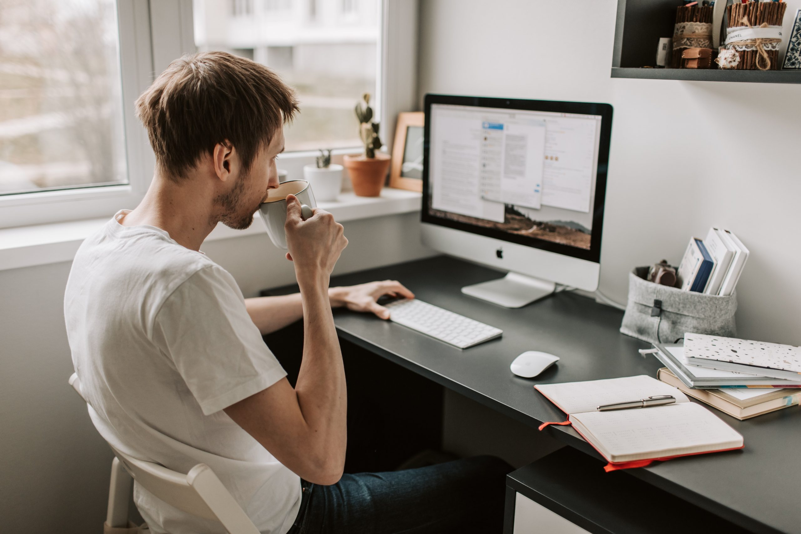 Man at computer sipping coffee
